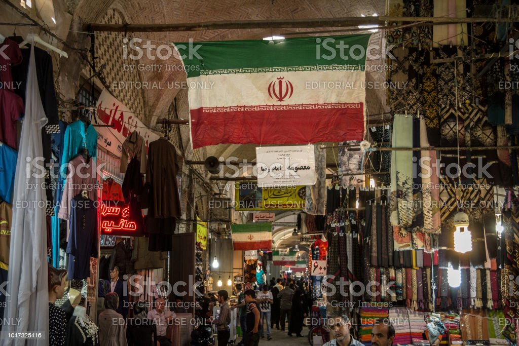 Street of the Isfahan bazar with an Iranian flag hanging, in a covered alley of the market. Symbol of the Persian architecture, it's a major landmark of the city stock photo