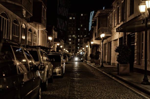 straße der alten nacht stadt mit pflasterstein, beleuchtet von straßenlaternen mit parkenden autos. - hofkleider stock-fotos und bilder