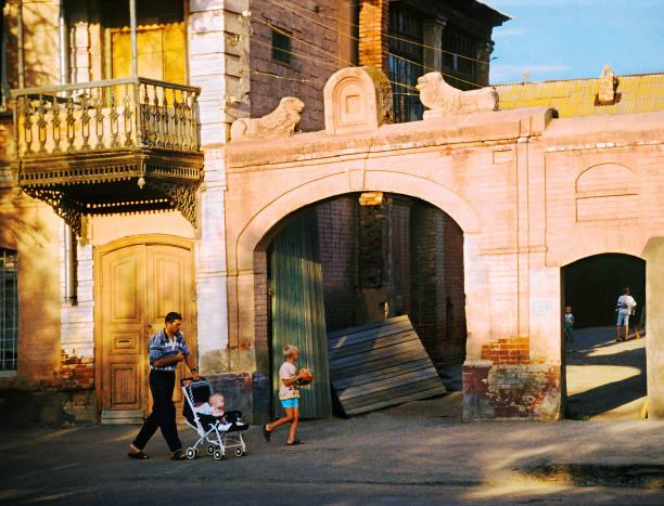 straße, altes haus, alte hof, papa kommt mit seinem sohn und einen kinderwagen rollt - typisch 90er stock-fotos und bilder