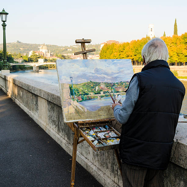 Street painter holding paintbrushes and painting Verona foto