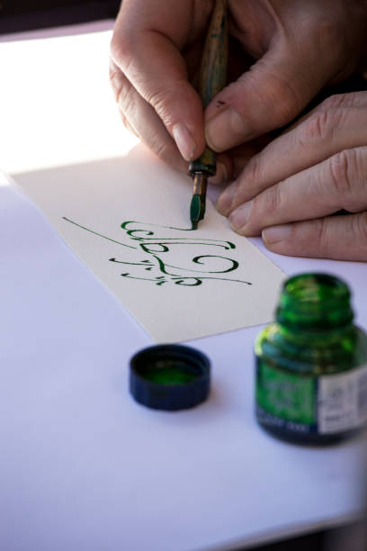 street painter writing a celtic name with green pen - karikaturen zeichnen stock-fotos und bilder