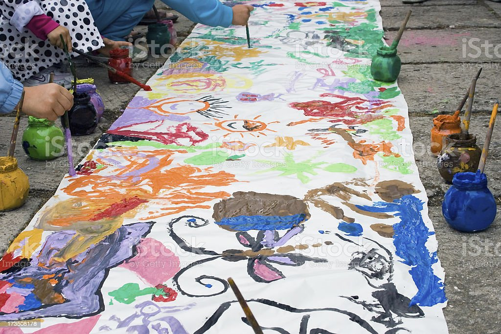 Paintings made by children on a long street lined paper, along the...