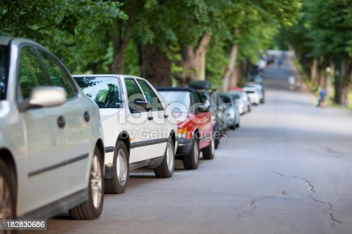 Street with long row of cars parked along a tree avenue.