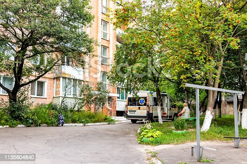 istock Street pavement in Rovno western city with outdoor park in summer and ambulance emergency truck on run-down old road 1135604840