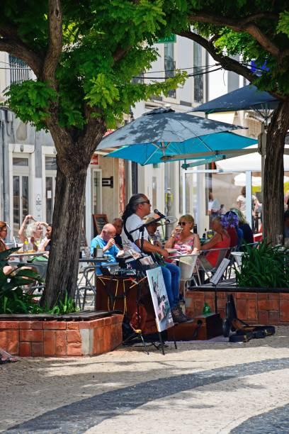 street performer and cafe, lagos, portugal. - esplanada portugal imagens e fotografias de stock