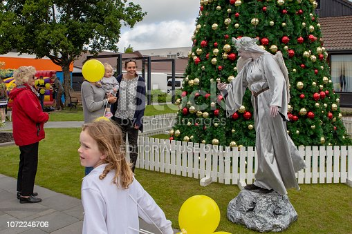 Rangiora, New Zealand: A street performer entertains people in front of a decorated Christmas tree