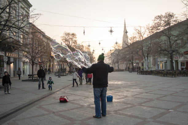 Novi Sad, Serbia - December 13, 2015: Street performer making soap bubbles in order to amuse people passing by pn Novi Sad main street, Zmaj Jovina Street performer blowin bubbles to impress children in a pedestrain street of Novi Sad, capital city of Voivodina, Serbia amuse stock pictures, royalty-free photos & images