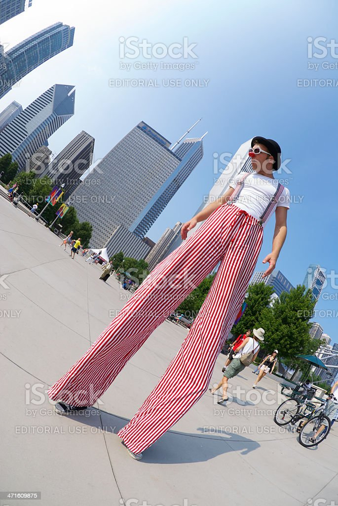 Street Performer Man on Stilts Walks by City Skyline stock photo