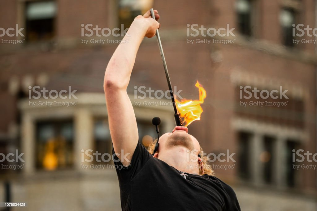 Street performer puts a lit fire stick into his mouth in the city of Amsterdam stock photo