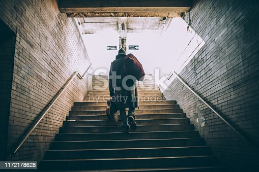 One man, young homeless man holding acoustic guitar, walking up the stairs, rear view.