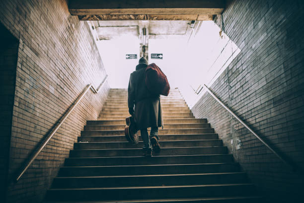 Street performer walking up the steps One man, young homeless man holding acoustic guitar, walking up the stairs, rear view. homelessness stock pictures, royalty-free photos & images