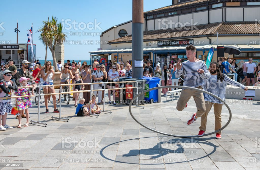Street performer with a metal ring at the seafront in Bournemouth, UK stock photo