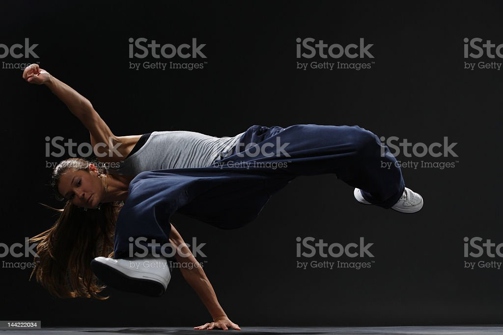 Street performer woman is break dancing in baggy pants royalty-free stock photo