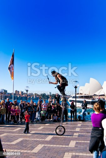 Sydney, Australia - August 14, 2010:  A street performer riding a tall unicycle enlists the help of a young boy with his performance to many tourists and onlookers.  He pays the boy several dollars for his assistance.