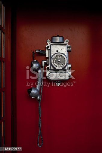 Street phone box. Old dirty and scratched telephone booth in red cabin