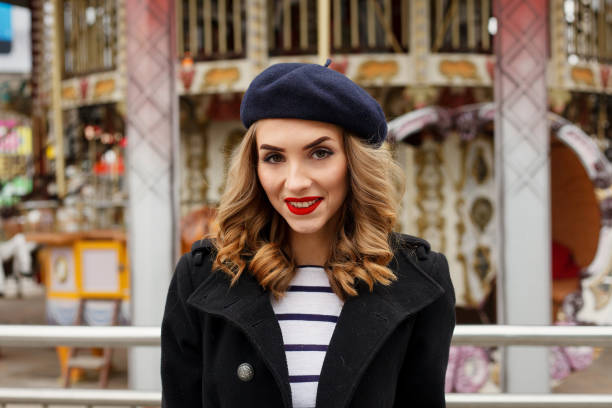 Street photo of young beautiful woman wearing stylish classic clothes. emotions, people, beauty and lifestyle concept - Girl Frenchwoman, against a merry-go-round. Street photo of young woman wearing stylish classic clothes. Female fashion concept. French style. beret stock pictures, royalty-free photos & images
