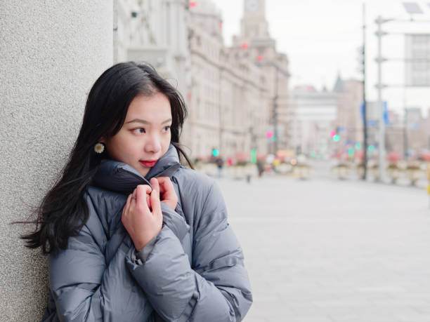 Street photography of beautiful young brunette woman in sunny winter city. Outdoor fashion portrait of glamour young Chinese stylish lady. Emotions, people, beauty and lifestyle concept. stock photo