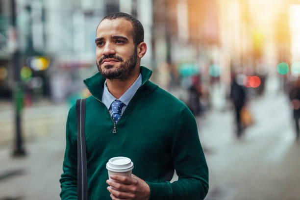 Street portrait of a young businessman holding a cup of coffee stock photo