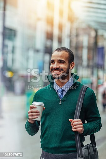 Street portrait of a young businessman holding a cup of coffee