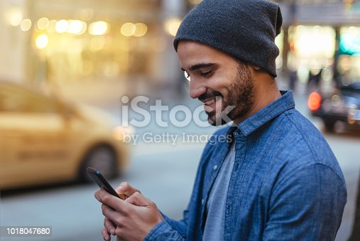 Street portrait of a young man holding mobile phone