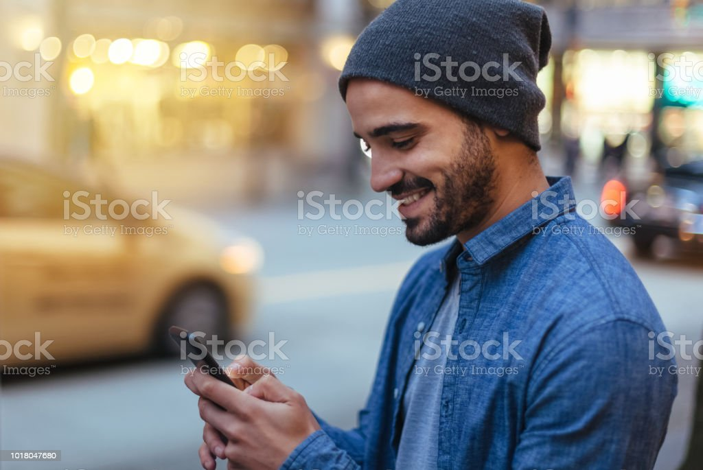 Street portrait of a young man holding mobile phone stock photo