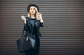 Street portrait of glamour sensual young stylish lady wearing trendy fall outfit. Blonde woman in black hat and leather jacket and bag.