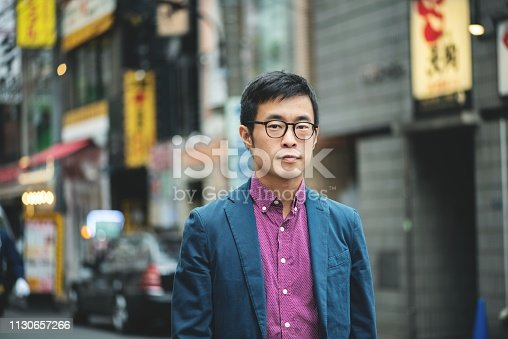 Outdoor portrait of a smartly dressed, mid-adult man at a shotengai in Tokyo.