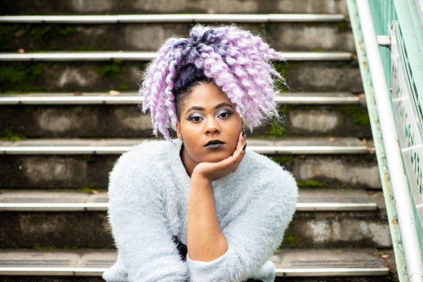 Street portrait of young woman with purple hair stock photo