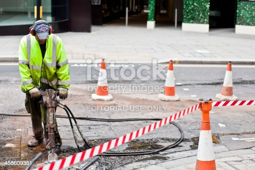London, United Kingdom - September 10, 2011: A construction worker uses a jackhammer digging on a street. The worker is standing on the road, blasting concrete with the jackhammer.