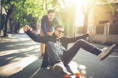 Two young men acting childlish and having fun with a longboard pushing one another down the street