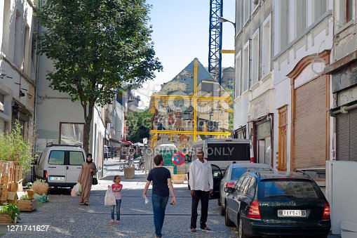 Street Rue du Chevreuil in Brussels at daytime. View into street where several people are walking. At left area is a woman with headscarf. In center are a child and two men, one is a black man. Cars are parked in street. In background are more people and also outside of a bar. Behind cars at right side are construction beams around abuilding with a mural of cartoon Boule and Bill by Roba which is part of official comic route in Brussels