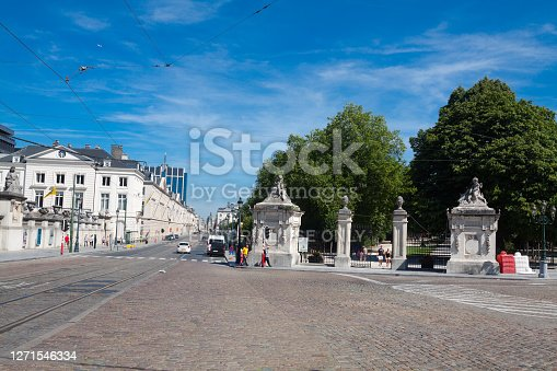 Street Rue Royale and Par of Brussels in summertime. A few people are walking in scene. At right side is entrance to public park. At left side are buildings
