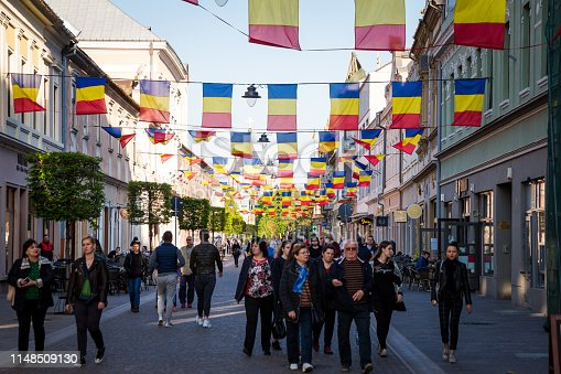 Oradea, Romania - 19 April, 2019: color image depicting people walking outdoors on the streets of the city centre of Oradea, a city in the Transylvania region of Romania. Romanian flags are strung across the street to celebrate an anniversary of this ancient city. Room for copy space.