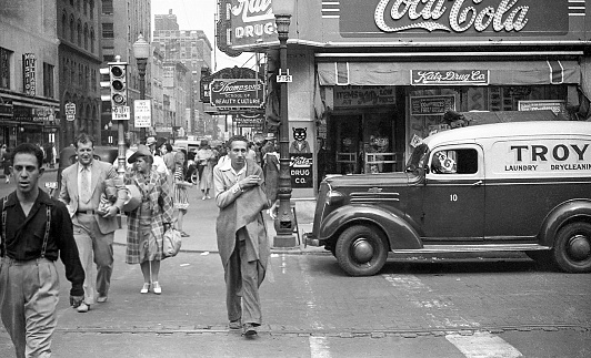 Downtown street scene with people and cars on street at 7th and Locust, Des Moines, Iowa, USA, 1939 including Katz Drug Store in the Edna Griffin Building. In 1948, ten years after this photo, the Katz Drug Store would be the scene of a civil rights incident when Edna Griffin, an African American, and her family were refused service.