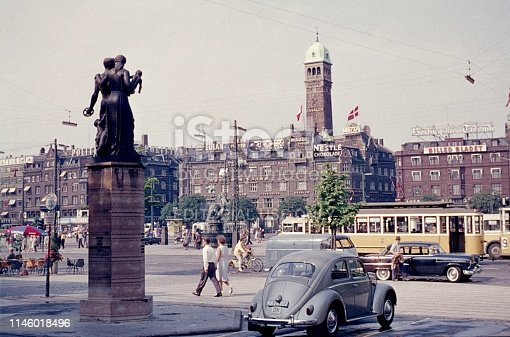 Indre By, Copenhagen, Denmark, 1960. Street scene at the Town Hall Square (Rådhuspladsen) in the Danish capital Copenhagen. Also: pedestrians, cars, tram, buildings, advertising signs and monuments.