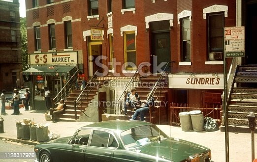 New York City, NY, USA, 1980. Street Scene in a New York City District (Bronx, Brooklyn ...). Also: Residents, buildings, shops and a parked cars.