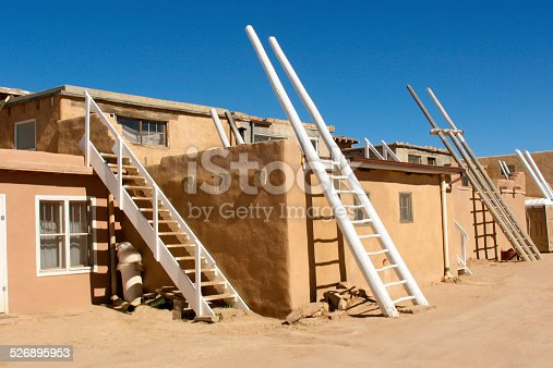 A street scene in Acoma Pueblo (Sky City), New Mexico, a Native American pueblo dating back to the 13th century. Traditional kiva ladders to enter via the roof are placed against the sides of buildings though nowadays there are doors at street level. Some copy space available.