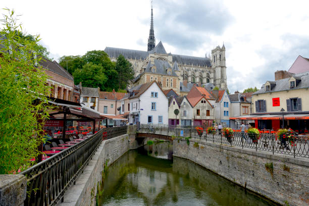 Street scene in Amiens, France. Amiens, France - July 27, 2017: Amiens Cathedral of Notre Dame and traditional houses on La place du Don Square at the embankment of Somme canal, Picardy, France. People on the background somme stock pictures, royalty-free photos & images