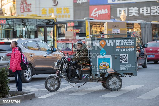 Beijing, China - December 4, 2015: A man driving on a heavily loaded gas powered tricycle on a cold winter day. He is doing car wash business. All kinds of bikes are an important means of transport in China's capital city.