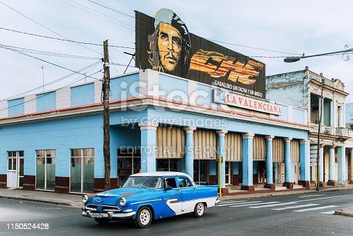 Cienfuegos, Cuba - March 22, 2015: Che Guevara banner on hispanic style building located on main street Paseo el Prado in Cienfuegos, Cuba. Blue vintage car driving along the road.