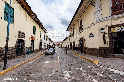 Cusco, Peru - Oct 17, 2018: A narrow street in central Cusco with old colonial architecture, cobblestone roads, and some people walking.