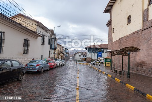 A narrow street in central Cusco with old colonial architecture, cobblestone roads, and some people walking.