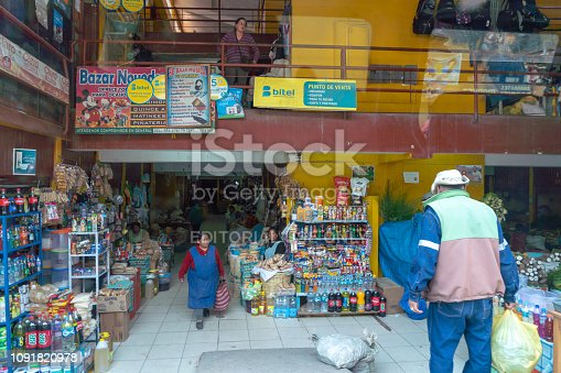 Cusco, Peru - Oct 17, 2018: A convenience store beside road.  A narrow street in central Cusco with old colonial architecture, cobblestone roads, and some people walking.