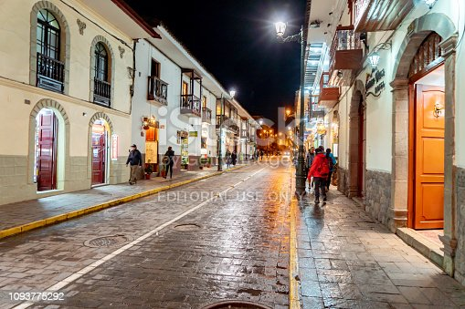 Cusco, Peru - Oct 14, 2018:  A narrow street in central Cusco with old colonial architecture, cobblestone roads, and some people walking.