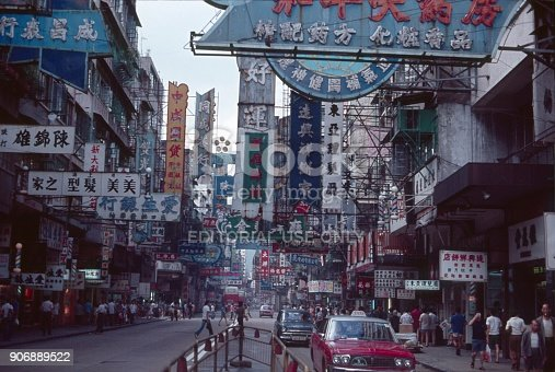 Hong Kong, China, 1977. Street scene in Hong Kong: characters, advertising, shops cars, buildings and pedestrians.