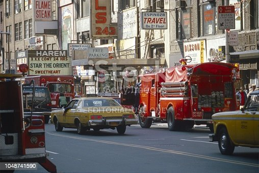 New York City, NYS, USA, 1980. Street scene on a side street near Broadway. Furthermore: fire brigade, traffic, shops, advertising, pedestrians and buildings.
