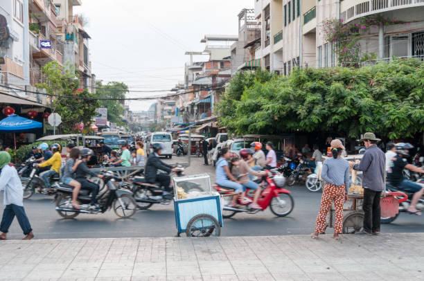 street scene in phnom penh, cambodia - motorbike, umbrella stock photos and pictures