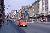 Neukölln, Berlin, Germany, 1979. Street scene with cars, passers-by and buildings, shops and subway station in Berlin's Neukölln district