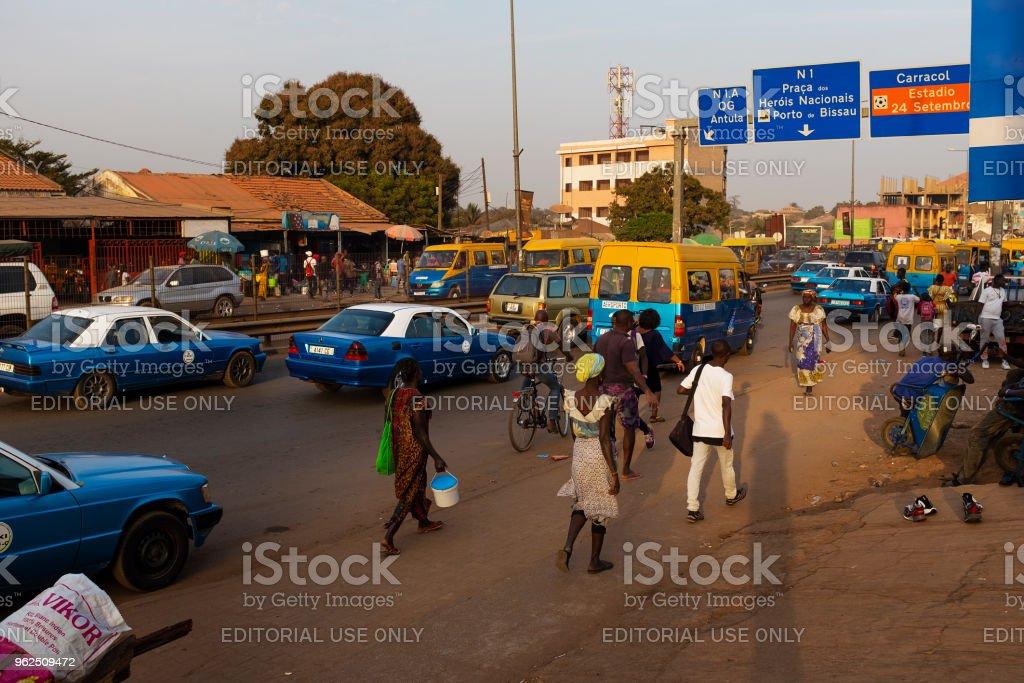 Cena de rua na cidade de Bissau, com as pessoas caminhando numa rua perto do mercado de Bittencourt, na Guiné-Bissau - Foto de stock de Adulto royalty-free