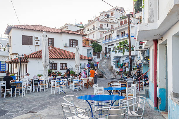 Street scene in the Greek village of Glossa on Skopelos Skopelos, Greece - July 24, 2015: Street scene in the Greek village of Glossa on the island of Skopelos as tourists start to gather in bars and restaurants. glossa stock pictures, royalty-free photos & images